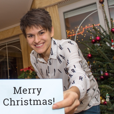 Young woman showing a Christmas card with a Christmas tree in the background Stock Photo