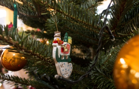 wish: Snowman on a sleigh filled with presents Christmas decoration on a Christmas tree