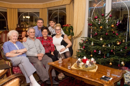 wish: Happy family posing with a Christmas tree and Christmas decoration in the background