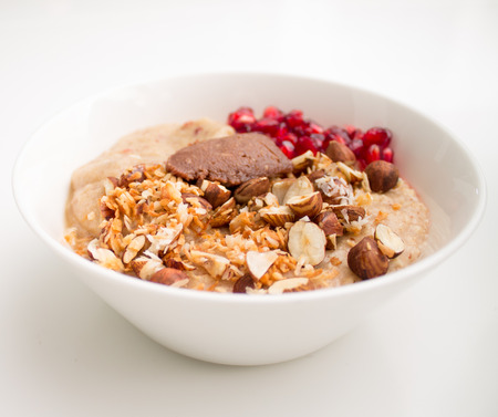 Bowl of oatmeal porridge with pomegranates, walnuts, almonds, coconut flakes, apple sauce and hazelnut butter against a white  photo