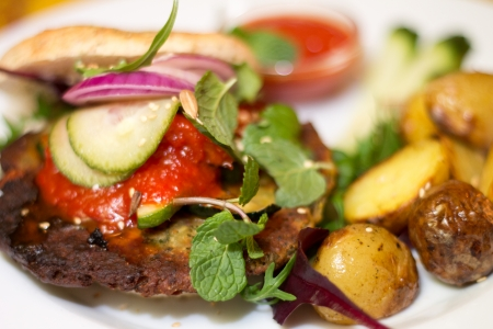 ovenbaked: Delicious vegan burger with chickpea patty, pickled cucumbers, onion, ketchup, grilled red peppers, mint leaves, salad, fresh vegetables and oven-baked potatoes on a white plate