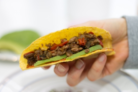 Close-up of hand holding a taco with vegetarian filling of corn, red pepper, beans, soy meat, avocado, dip on blurred light background photo
