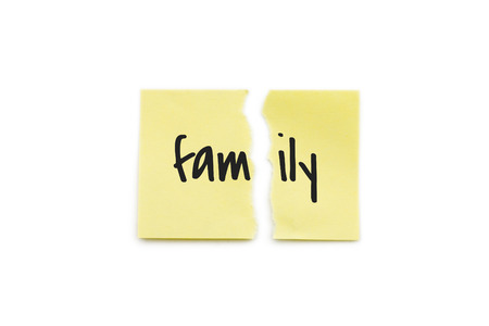 Yellow paper note torn in two with the word family, isolated on white background