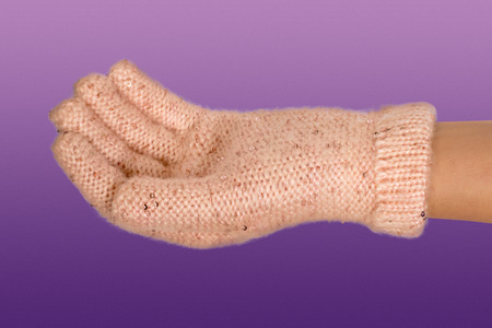 pink fur: Female holding hand in pink fur mitten keep Christmas on purple background Stock Photo