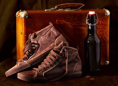 Old suitcase, sneakers, bottle wine, coins. Vintage style photo