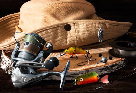 Fishing tackle. Hook, hat, fishing reel, lures on darken wooden background. Still life