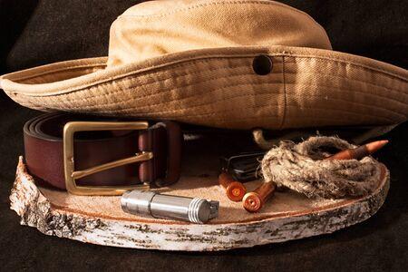 Hunting. Hat, knife, bullet, rope, shell, belt, lighter, on darken wooden background. Still life Imagens