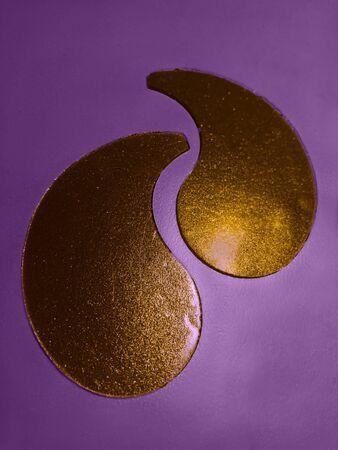 Gold Collagen patch for eyes on violet background.