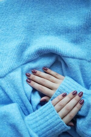 Violet manicure and blue sweater. Imagens