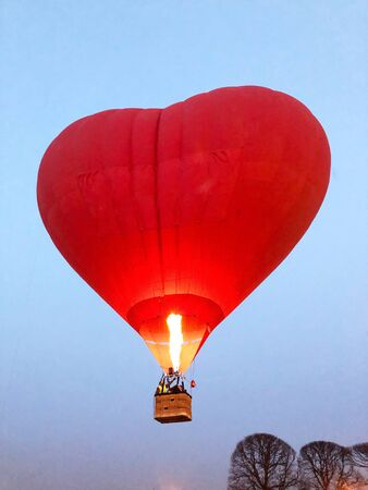 Red balloon in the heart shape at the blue sky.