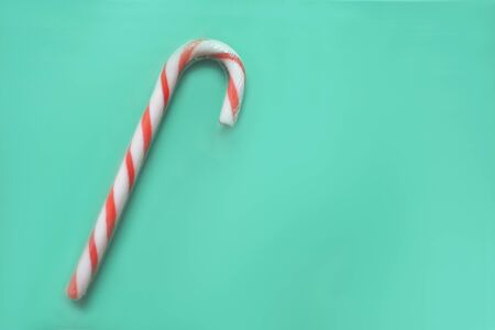 Christmas candy cane on green background.