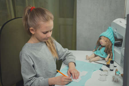 little girl is engaged in needlework at home