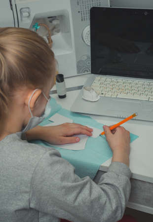 a girl is sitting at a table learning to sew a dress for a doll from video lessons at home