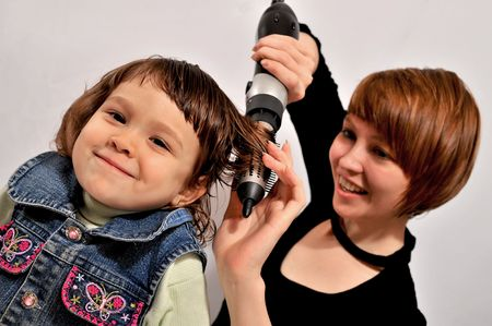 The woman dries girls hair. The child smiles with pleasure photo
