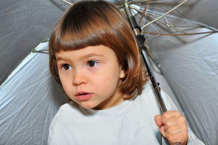 sadly: ragazza sembra purtroppo fuori sotto un ombrello  Archivio Fotografico