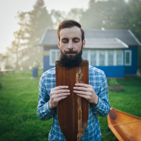 double reed: handsome man holding wooden canoe paddle Stock Photo