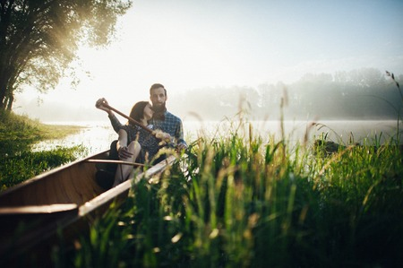 double reed: wife with husband sitting in canoe  in morning