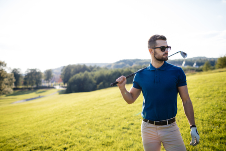 Full length view of man in cap holding golf club and hitting bal