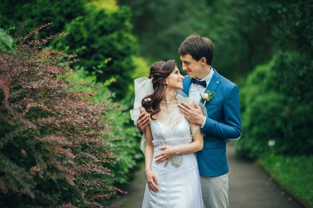 Confident elegant groom and beautiful shy bride holding hands ou