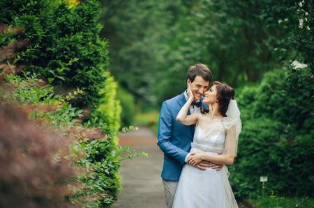 Happy smiling stylish bride and groom walking in the summer gree