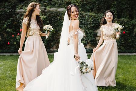 Braut mit Brautjungfern am Park am Hochzeitstag