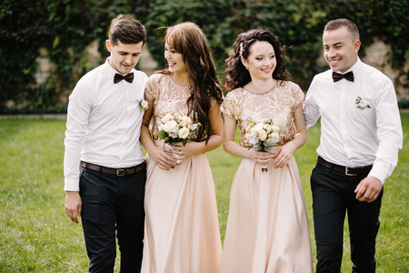 Newlywed couple, bridesmaids and groomsmen having fun outdoors