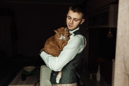 Cat hold by a groom while  preparing for wedding ceremony