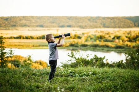 little boy looking into telescope eyepiece