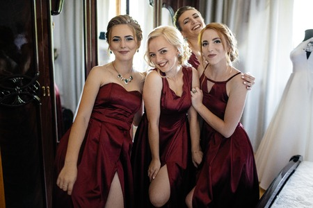 Lovely bride and bridesmaids next to the big window Imagens