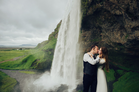 Bride and groom walking in Iceland. Icelandic waterfall on the b Stock Photo