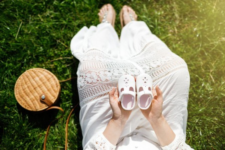 Young happy pregnant woman relaxing in nature. Close up of pregnant belly in nature.