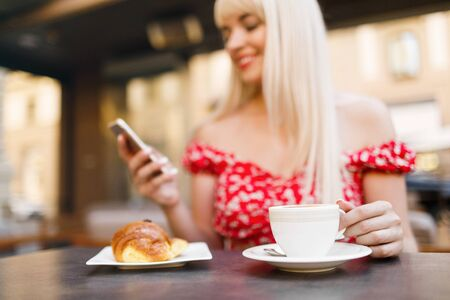 Young woman having italian breakfast with croissant and coffee a
