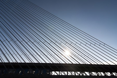 Modern bridge steel ropes constructions on sky  background