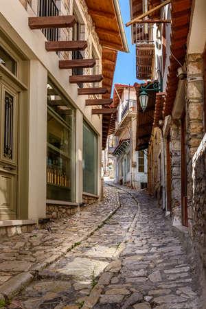 Traditional architecture in a narrow cobblestoned street in Dimitsana village, Greece.