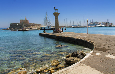 Lighthouse and deer statue in Mandraki harbor, where the Colossus of Rhodes stood, Greece photo.