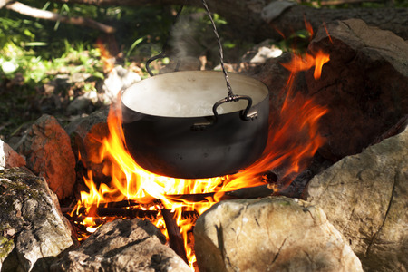 Pot water on the fire, tourists kettle on hot campfire. Camping photo.
