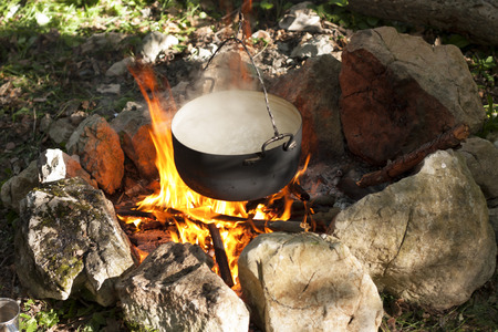 Pot water on the fire, tourists kettle on hot campfire. Camping photo. photo