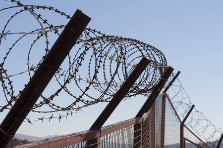 link fence: Security with a barbed wire fence photo. Protection concept design. Stock Photo
