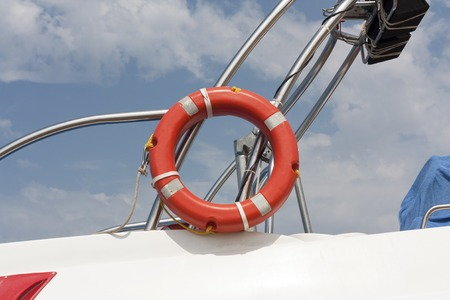 safe water: Safe water support aid circle with rope. Rescue red life buoy on sky background of ship or boat. Helpful object.