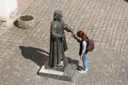 Girl making a wish to statue of prince Podolsky Fedir Koryatovych (1331-1414) in castle Palanok, Mukachevo, Ukraine photo: MUKACHEVO,UKRAINE - APRIL 1,2017 Редакционное