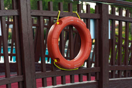 Orange lifebuoy with rope on a wooden pier near sea. Close up of lifebuoy on wooden pier at the beach photo