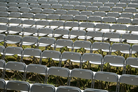Rows of empty white folding chairs 免版税图像