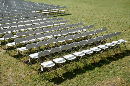 Rows of empty white folding chairs Archivio Fotografico