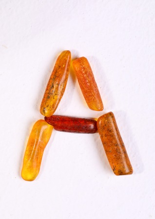 Baltic amber stones on white background. Letter A
