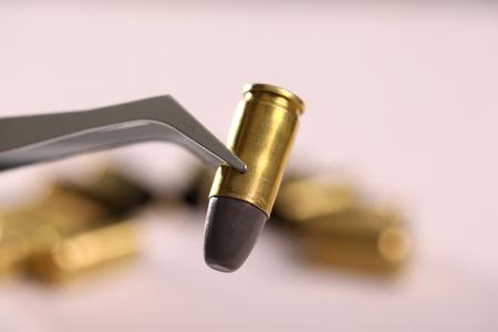 Gun bullet holding with tweezer Zdjęcie Seryjne