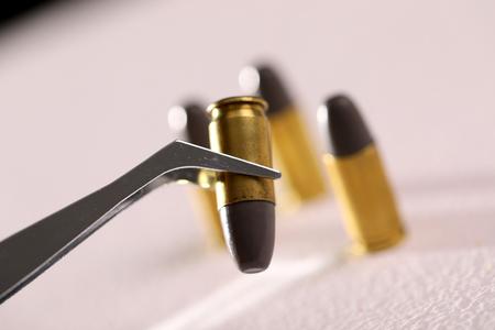 Gun bullet holding with tweezer 写真素材