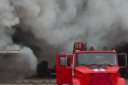 fire fighting and assistance. fire engine in the smoke from the fire