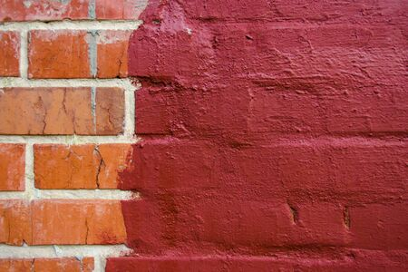 red brickwork half painted in dark red paint
