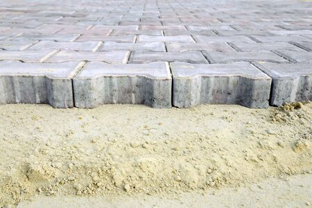 pavement renovation. Paving bricks ready for construction work. Laying paving slabs on a city square, sidewalk Stock Photo