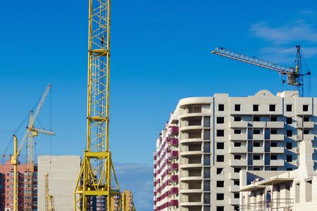 construction cranes on the background of multi-apartment buildings under construction. The concept of construction of apartment buildings houses 写真素材